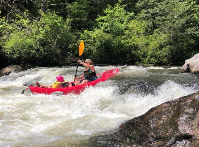 woman and child rafting along the waves on the Chattooga River in Long Creek South Carolina